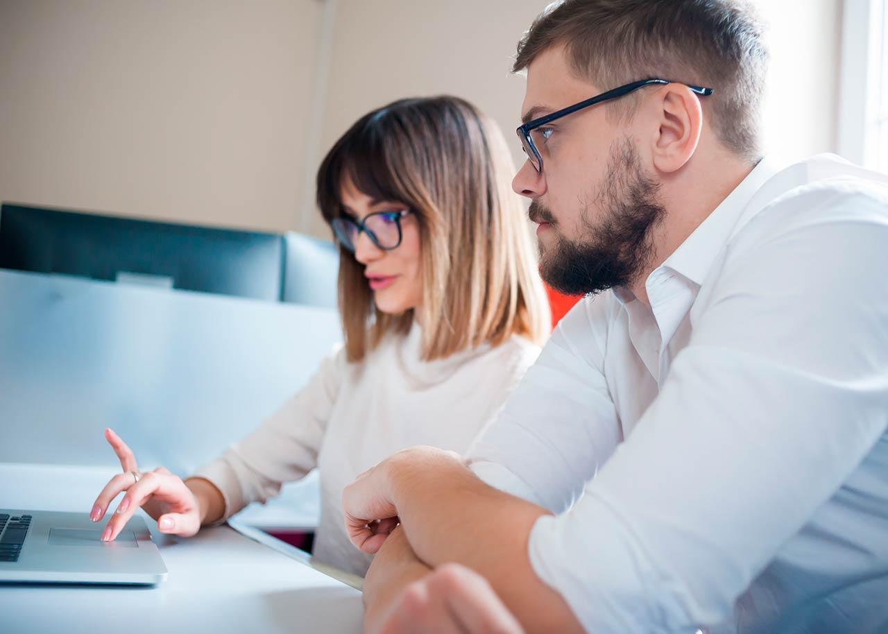 Henkilöitä käyttämässä automaattista maksuvalvontaa tietokoneella